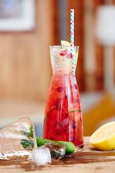 Lemoniada z ogórków z żurawiną składająca się z soku z cytryny, syropu z arbuza i wody sodowej w szklanym zlewce zbliżenie drewniany stół