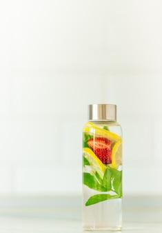 Lemoniada z plastrami mięty, cytryny i truskawek w słoiku nadającym się do recyklingu w białej letniej przestrzeni kopii w tle kuchni