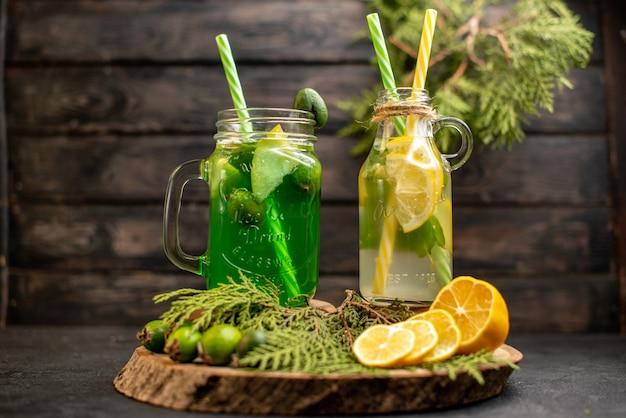 Lemoniada z widokiem z przodu z feijoa i cytryną na drewnianej desce pokroić cytryny i feijoa na ciemnej izolowanej powierzchni
