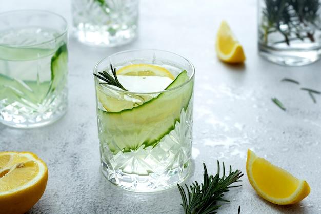 Lemoniada ze świeżymi ogórkami, cytryną i rozmarynem w szklankach na jasnym tle