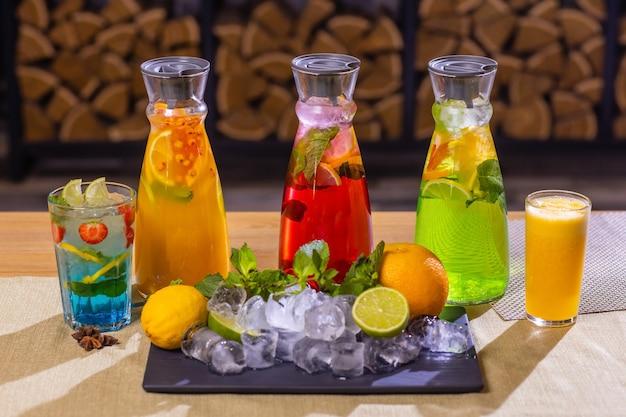 Lemoniady owocowe i jagodowe na drewnianej tacy ze świerkiem.