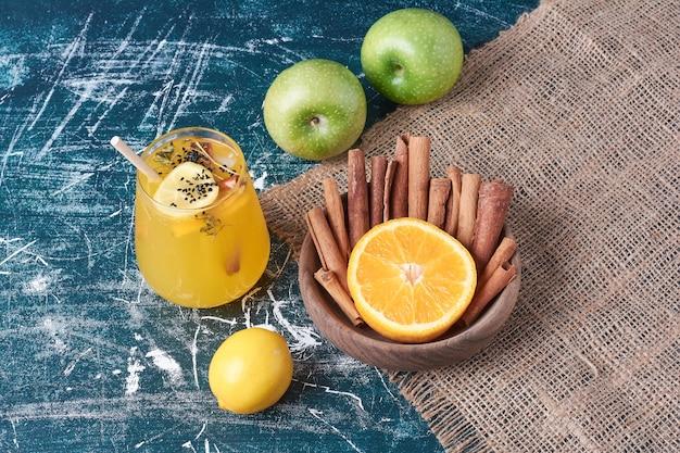 Lemonnd cynamons przy filiżance napoju na niebiesko.