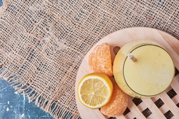 Lemonnd mandarynki przy filiżance napoju na niebiesko.