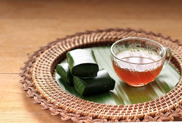 Lemper ayam podawany z herbatą. lemper to indonezyjska przekąska z kleistego ryżu nadziewana sezonowanym posiekanym kurczakiem zawinięta w liść bananowca, podawana na herbatę. wybrany fokus