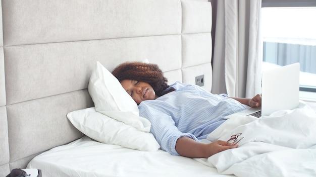 Leniwa gruba kobieta zasnęła w łóżku, pracując na laptopie