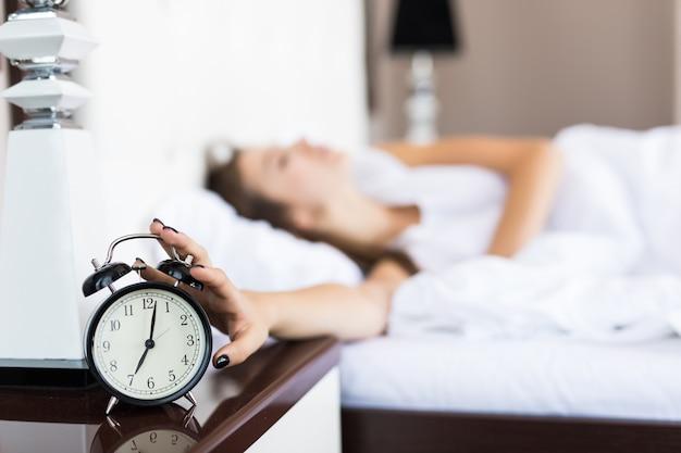 Leniwa kobieta nadal leży po tym, jak rano dzwoni budzik