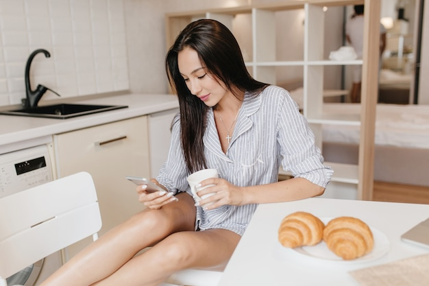 Leniwa kobieta o lekko opalonej skórze podczas śniadania ze smartfonem z pysznymi rogalikami