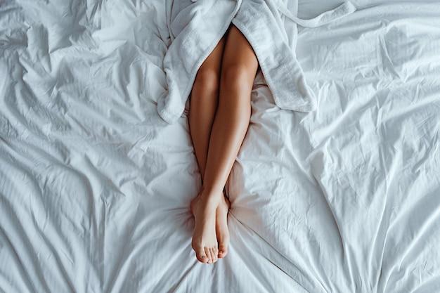 Leniwa kobieta ubrana w szlafrok o smukłych, długich, pięknych nogach leżąca na białym łóżku i relaksująca się w przytulnej, komfortowej sypialni w pokoju hotelowym