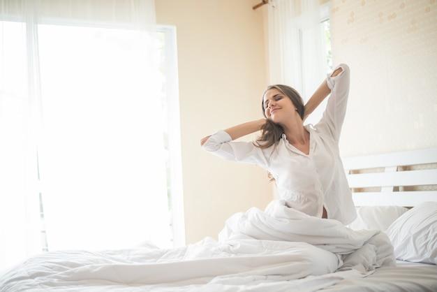 Leniwa młoda kobieta siedzi w sypialni