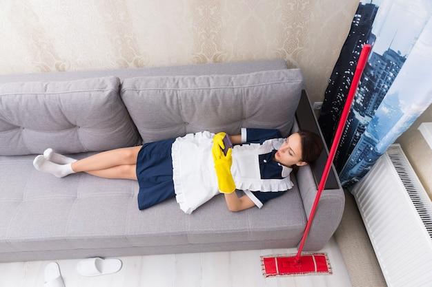 Leniwa praca nieśmiała gospodyni w mundurze robi sobie przerwę leżąc na plecach na kanapie z mopem obok niej sprawdzając swój telefon komórkowy, widok z góry