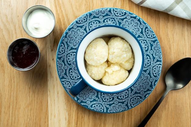 Leniwe pierogi z twarogiem w niebieskiej misce ze śmietaną i dżemem truskawkowym. widok z góry. jedzenie leżało płasko. kuchnia ukraińska.
