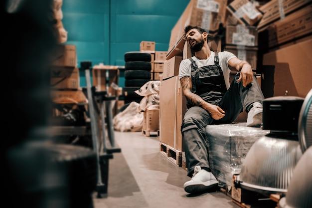 Leniwy brodaty wytatuowany pracownik śpi na pudłach w godzinach pracy. wnętrze do przechowywania.