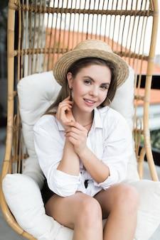 Leniwy czas w wygodnym fotelu. piękna młoda kobieta relaks w dużym wygodnym fotelu na tarasie jej domu