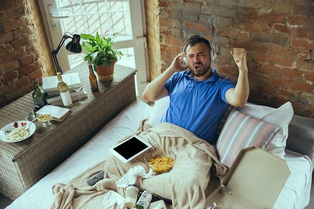 Leniwy człowiek spędzający całe życie w swoim łóżku otoczony bałaganem