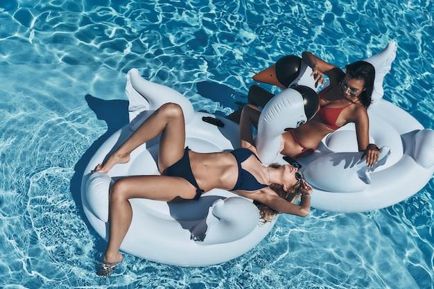 Leniwy letni dzień. widok z góry na dwie atrakcyjne młode kobiety w bikini, patrzące na siebie, unoszące się na dużych nadmuchiwanych łabędziach