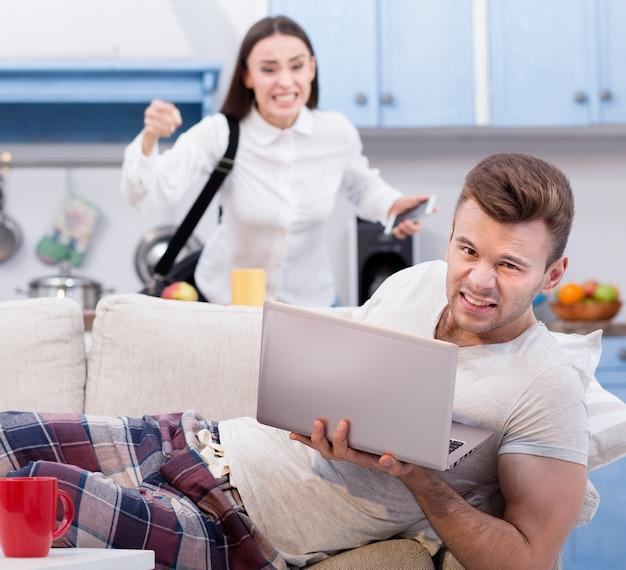 Leniwy mąż na kanapie i jego wściekła żona, która idzie do pracy.