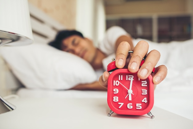 Leniwy mężczyzna budzi się w swojej sypialni