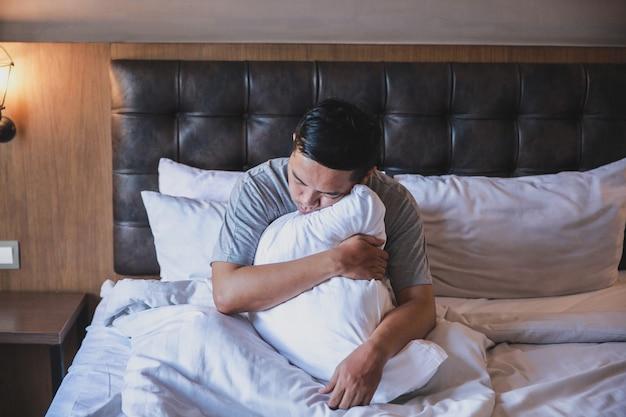 Leniwy mężczyzna śpi siedząc i przytulając poduszkę na łóżku