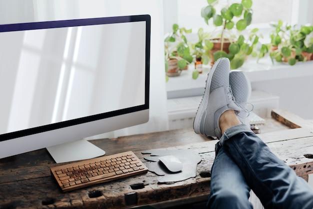 Leniwy mężczyzna stawiający nogi na stanowisku pracy