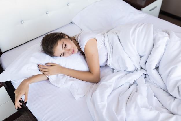 Leniwy poranny weekend dla uroczej brunetki w szerokim łóżku z białą pościelą w hotelu lub modnym apartamencie