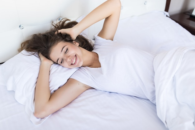 Leniwy poranny weekend dla uśmiechniętej brunetki modelki w szerokim łóżku z białą pościelą w hotelu lub modnym mieszkaniu