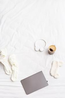 Leniwy weekendowy poranek, leżak na płasko z laptopem, ciepłe skarpetki, filiżanka kawy, słuchawki bezprzewodowe, maska do spania na łóżku