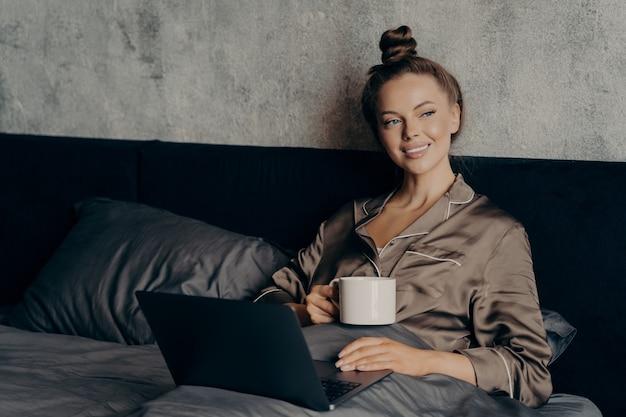 Leniwy zrelaksowany poranek. uśmiechnięta piękna młoda kobieta leżąca w łóżku w satynowej piżamie z filiżanką kawy w dłoni podczas sprawdzania ostatnich wiadomości w internecie online na laptopie, ciesząc się wolnym czasem w domu