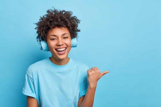 Lepiej podążaj tą drogą. uśmiechnięta ciemnoskóra afroamerykanka wskazuje kciukiem, sugeruje miejsce do odwiedzenia, nosi bezprzewodowe słuchawki, ubrana swobodnie, lubi słuchać muzyki przez słuchawki