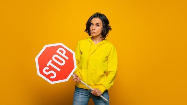 """Lepiej przestań! niezadowolona dziewczyna o surowej twarzy, ubrana w żółtą bluzę, protestująca z napisem """"stop"""" w dłoniach."""