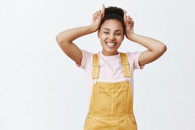 Lepiej uważaj na mnie. portret radosnej pewnej siebie i pięknej afroamerykanki w stylowych żółtych kombinezonach, pokazująca rogi z palcami na głowie, szeroko uśmiechnięta, uparta