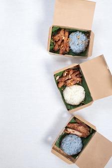 Lepki ryż z grillowaną wieprzowiną i smażoną wieprzowiną włóż w brązowe papierowe pudełko, połóż na białym obrusie, pudełku na żywność, tajskie jedzenie.