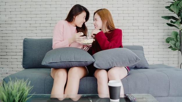 Lesbijska azjatycka para ogląda tv śmiać się i je popkorn w pokoju w domu, słodka para cieszy się