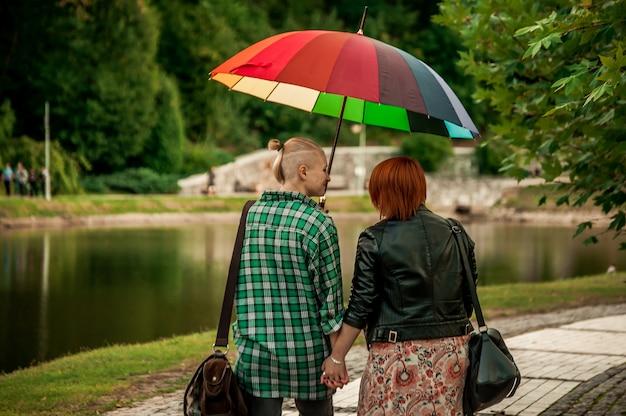 Lesbijska para pod tęcza parasolem w parku