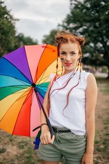 Lesbijska rudowłosa dziewczyna z warkoczykami, flagą lgbt na twarzy, kolorową torbą i parasolem pozowanie na zewnątrz