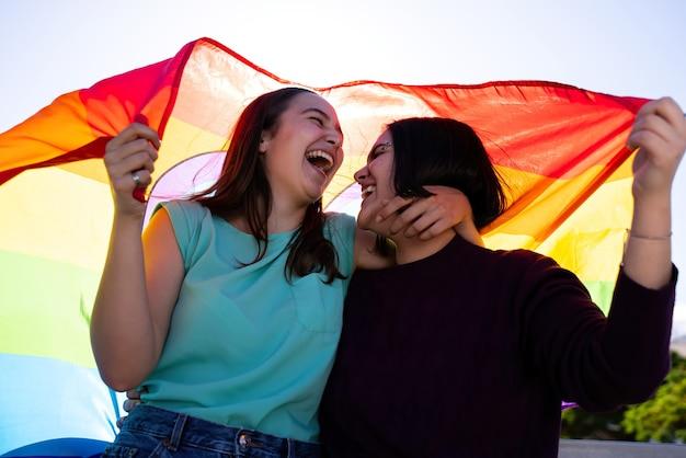 Lesbijskie dziewczyny bawią się malując się i z flagą lgtb na koncepcji lgtb na dzień dumy