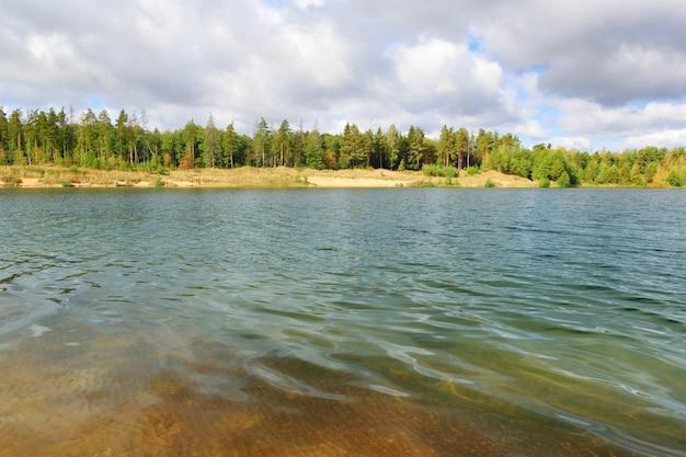 Leśne jezioro pod błękitnym pochmurnym niebem