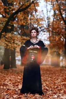 Leśny elf, wróżka, wiedźma w jesiennym lesie z latarnią. koncepcja halloween.