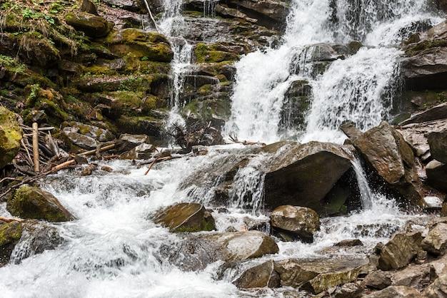 Leśny wodospad i skały pokryte mchem. karpaty, szypr, ukraina, europa.
