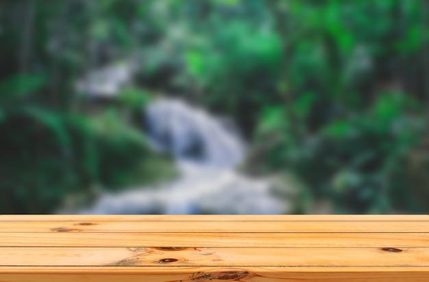 Leśny wodospad tło z gładkim drewnianym stołem produktowym