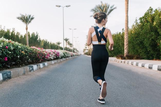 Letni czas radosnej młodej kobiety z tyłu biegnącej ulicą z palmami, kolorowe kwiaty w tropikalnym mieście. pogodny nastrój, dobra zabawa, trening, słoneczny poranek, atrakcyjna modelka.