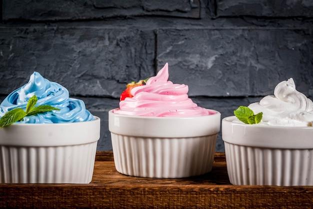 Letni deser zdrowej diety, mrożony jogurt waniliowy i jagodowy lub lody miękkie w białych misach