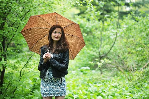 Letni deszcz. kobieta w ogrodzie.