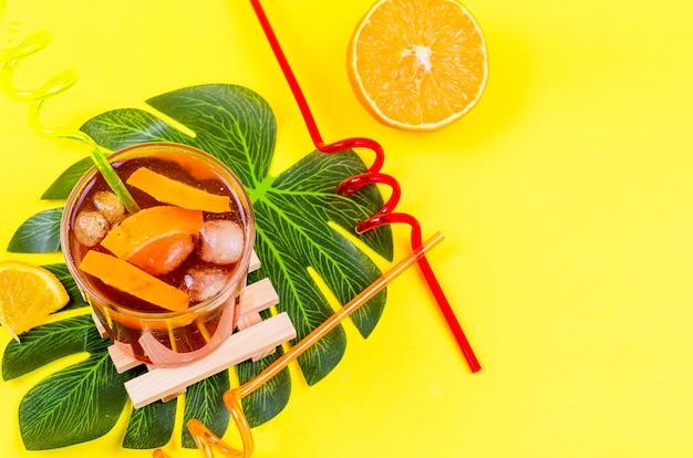 Letni domowy zimny czerwony koktajl sangria z pomarańczy i lodu w szkle na żółtym tle