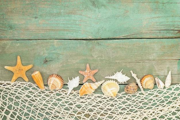 Letni drewniany stół z siatką z muszelek i rozgwiazd