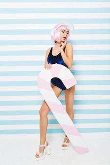 Letni gorący modny wygląd niesamowitej seksownej młodej kobiety w stroju kąpielowym, z różowymi obciętymi włosami, na obcasach, cieszącej się na biało-niebieskiej ścianie w paski. plaża, wakacje, wypoczynek, radość.