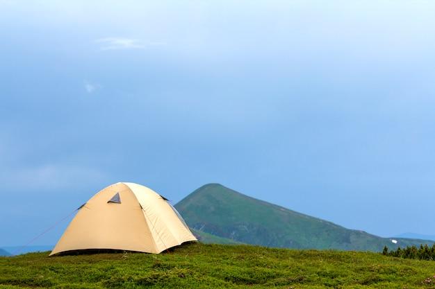 Letni jasny słoneczny dzień. mały turystyczny namiot na trawiastej dolinie na odległych mglistych zielonych górach pod jasną błękitną bezchmurną sceną nieba. koncepcja turystyki, turystyki pieszej, kempingu i piękna przyrody.