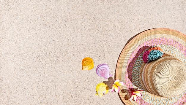 Letni kapelusz i muszle na piasku, widok z góry, kopia przestrzeń