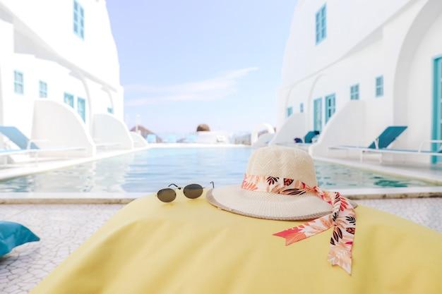 Letni kapelusz i okulary przeciwsłoneczne na żółtej torebce z fasolą z tłem basenu i niebem