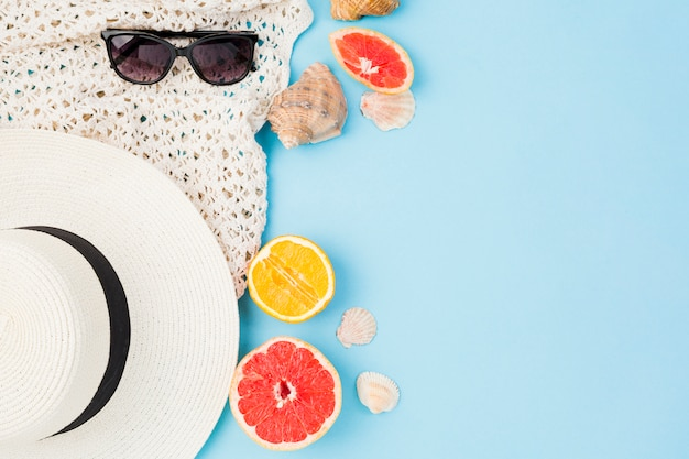 Letni kapelusz i okulary przeciwsłoneczne w pobliżu owoców i muszelek