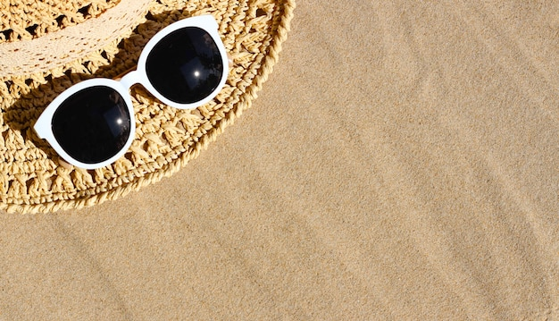 Letni kapelusz z białymi okularami przeciwsłonecznymi na piasku. koncepcja tło lato.